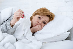 妇女在与温度计狂热微弱的遭受的冬天冷的流感病毒的床上 免版税库存图片