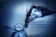 妇女在与眼睛的床上打开了遭受的失眠和失眠 库存图片