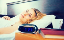 妇女在与眼睛的床上说谎开放在卧室在时钟和书附近 库存图片