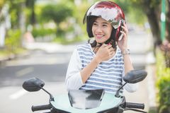 妇女在乘坐摩托车前投入了她的盔甲  免版税库存图片