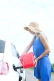 妇女在乡下公路的换装燃料汽车侧视图  免版税图库摄影