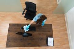 妇女在书桌的清洁键盘 免版税库存图片