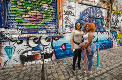 妇女在云香Denoyez的五颜六色的街道画前面摆在巴黎 免版税库存图片