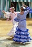 妇女在五颜六色的佛拉明柯舞曲礼服和跳舞穿戴了在塞维利亚4月市场 库存图片