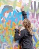 妇女在五颜六色的街道画墙壁写 免版税库存照片