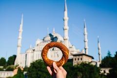 妇女在伊斯坦布尔,土耳其拿着一个传统iretsky百吉卷被命名Simit在蓝色清真寺的背景 免版税库存图片