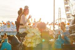 妇女在传统服装骑乘马支架在日落和庆祝穿戴了在SevilleÂ的4月市场 免版税库存照片