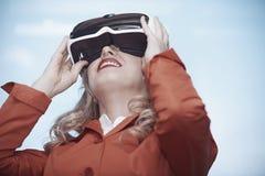 妇女在佩带虚拟现实耳机的办公室 免版税库存图片