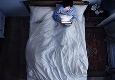 妇女在使用一个数字式设备的床上在黑暗 免版税库存图片