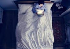 妇女在使用一个数字式设备的床上在黑暗 库存图片