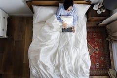 妇女在使用一个数字式设备的床上 库存图片