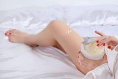 妇女在使用奶油的床上身体的 免版税库存照片