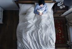妇女在使用她的手机的床上在黑暗 图库摄影