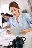 妇女在使用片剂和照相机的办公室 免版税库存照片