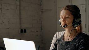妇女在使用耳机的电话中心和讲话与人 股票录像