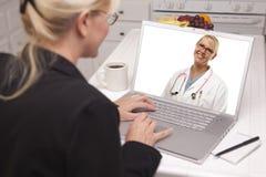 妇女在使用膝上型计算机的厨房里-在网上与护士或医生 免版税库存图片