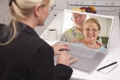 妇女在使用膝上型计算机的厨房里-在网上与资深夫妇 库存图片