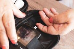 妇女在使用针以后测试与glucometer的葡萄糖水平抽血液 库存图片