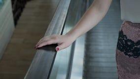 妇女在保持栏杆的自动扶梯乘坐 股票视频