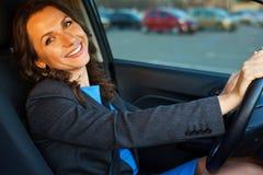 妇女在停车处的一辆汽车坐在购物中心附近 免版税库存照片