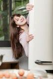 妇女在偷看从一开放冰箱和微笑的调查的后面门的厨房里照相机 免版税库存图片
