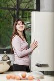 妇女在偷看从一开放冰箱和微笑的调查的后面门的厨房里照相机 库存照片