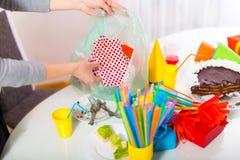 妇女在儿童的生日以后清洗混乱 免版税库存图片