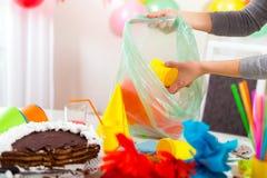 妇女在儿童的生日以后清洗混乱 库存照片