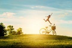 妇女在公园享受假日 她跳充满幸福 免版税库存图片