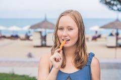 妇女在公园吃油煎的白薯 背景汉堡干酪鸡概念黄瓜深鱼食物油煎了旧货莴苣木三明治的蕃茄 图库摄影