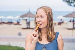 妇女在公园吃油煎的白薯 背景汉堡干酪鸡概念黄瓜深鱼食物油煎了旧货莴苣木三明治的蕃茄 免版税库存图片