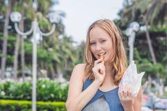 妇女在公园吃油煎的白薯 背景汉堡干酪鸡概念黄瓜深鱼食物油煎了旧货莴苣木三明治的蕃茄 免版税图库摄影