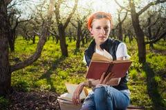 妇女在公园室外与片剂和书 免版税库存图片