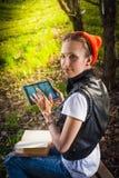 妇女在公园室外与片剂和书 免版税库存照片