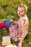 妇女在公园室外与片剂和书 免版税图库摄影