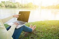 妇女在公园的点膝上型计算机 库存照片