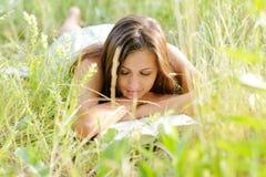 妇女在公园读了书 免版税库存照片