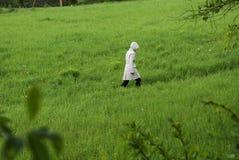 妇女在军用防水短大衣惨淡的天 库存照片