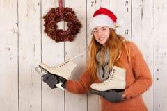 妇女在冬天与滑冰和帽子圣诞老人 免版税库存图片