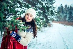 妇女在冬天森林里拿着一杯咖啡 库存照片