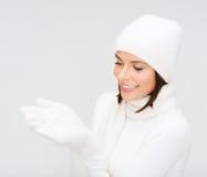 妇女在冬天穿衣与某事在棕榈 免版税库存照片