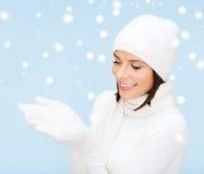 妇女在冬天穿衣与某事在棕榈 库存照片