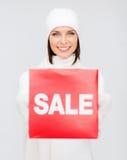 妇女在冬天穿衣与红色销售标志 免版税库存照片