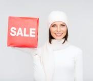妇女在冬天穿衣与红色销售标志 库存图片