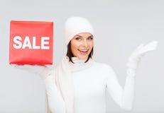 妇女在冬天穿衣与红色销售标志 免版税图库摄影