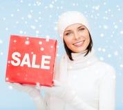 妇女在冬天穿衣与红色销售标志 免版税库存图片