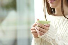 妇女在冬天递拿着一个热的咖啡杯 库存照片