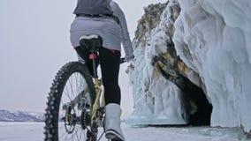 妇女在冰洞穴附近骑自行车 与冰洞和冰柱的岩石是非常美丽的 女孩打扮 股票视频