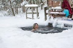 妇女在冰的孔游泳在一个冬天 库存图片