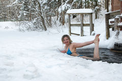 妇女在冰的孔游泳在一个冬天 免版税库存图片